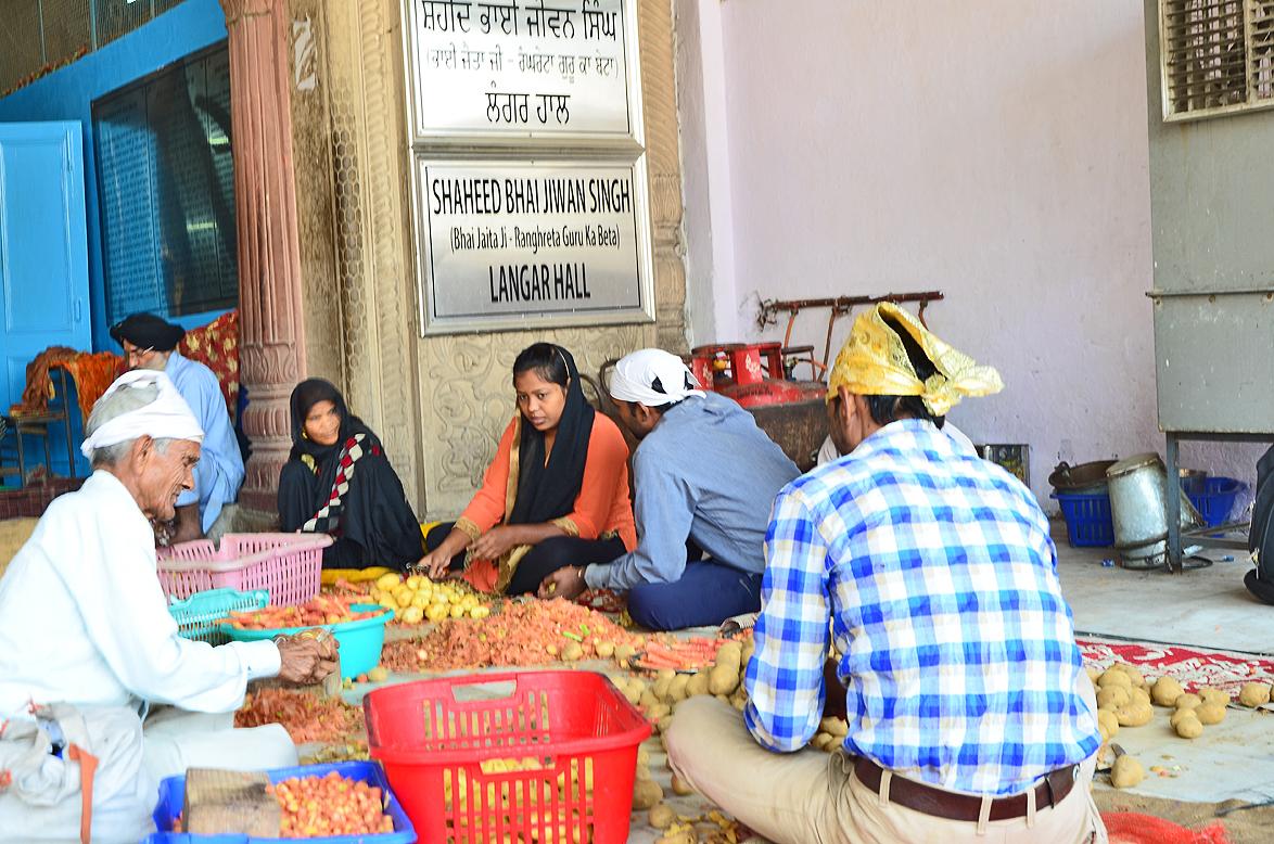 Volunteers prepare food for a langar at Gurudwara Sis Ganj Sahib