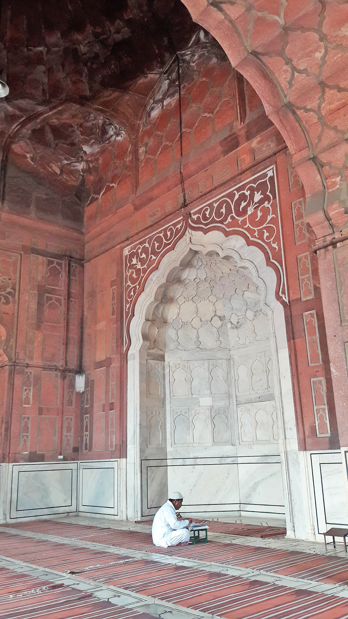 A worshipper prays, facing Mecca, at the Jama Masjid