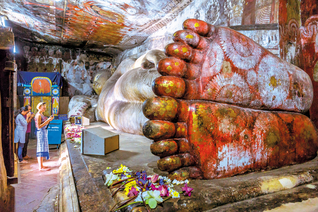 Reclining Buddha at the Dambulla Cave Temple in Sri Lanka. Dating back to the 3rd century BCE, this five-cave complex is still functional as a Buddhist temple. The reclining Buddha is one of 157 statues in the complex.