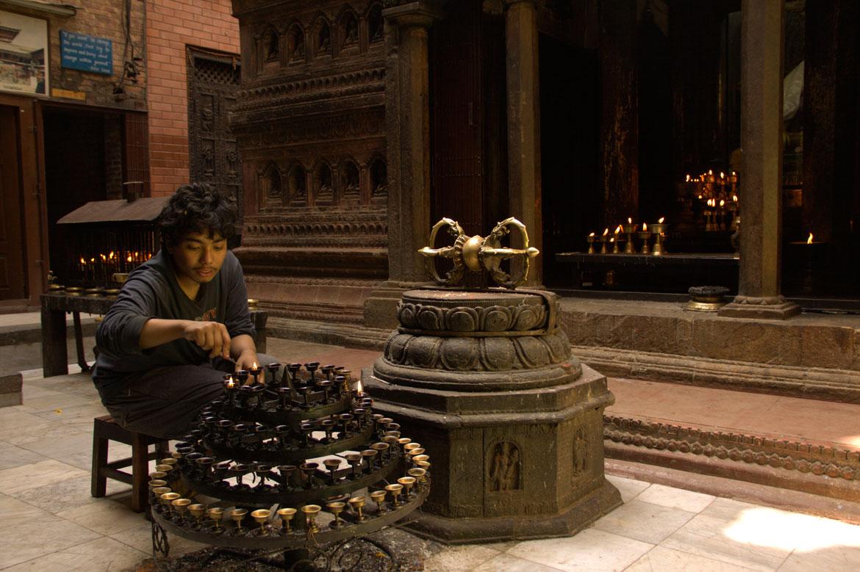 The Sakya god guardian of Mahabaudha lights lamps before the evening arati