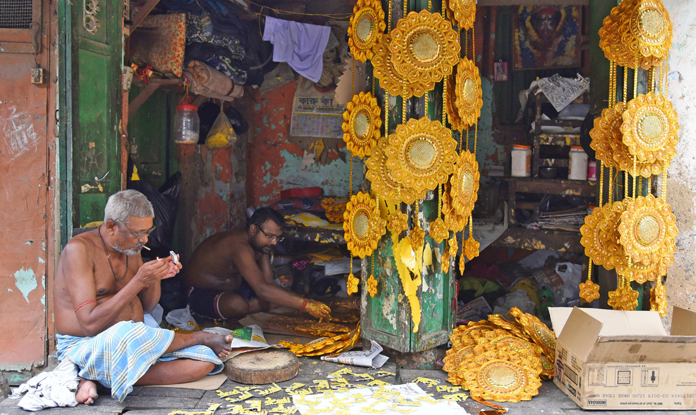 Sellers who keep Durga Puja decorations in Kumartuli take a small break before work starts again