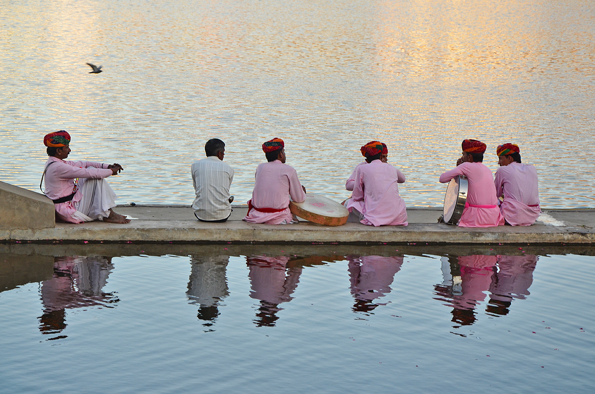 A troupe of traditional performers take rest by the lakeside