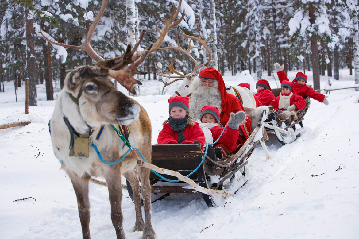 Santa and his elves on a reindeer sled at Santa Claus Village