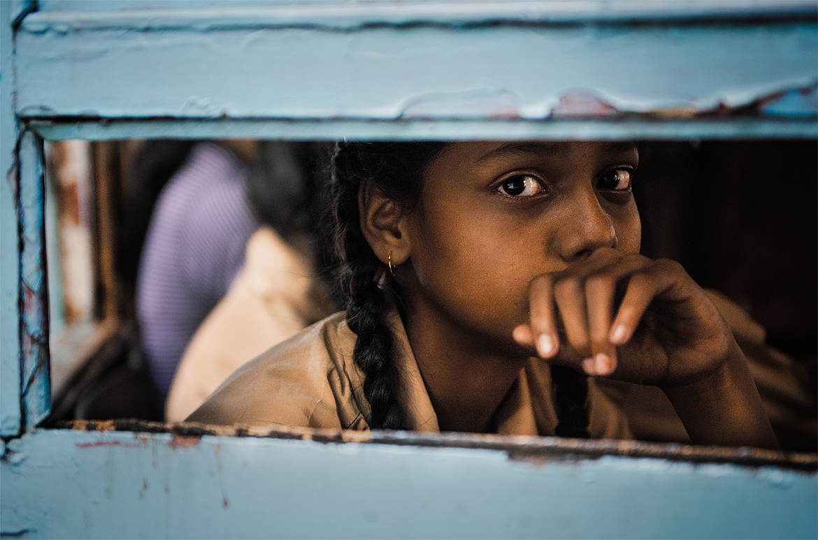 A young girl gazes into the camera through the tram's window