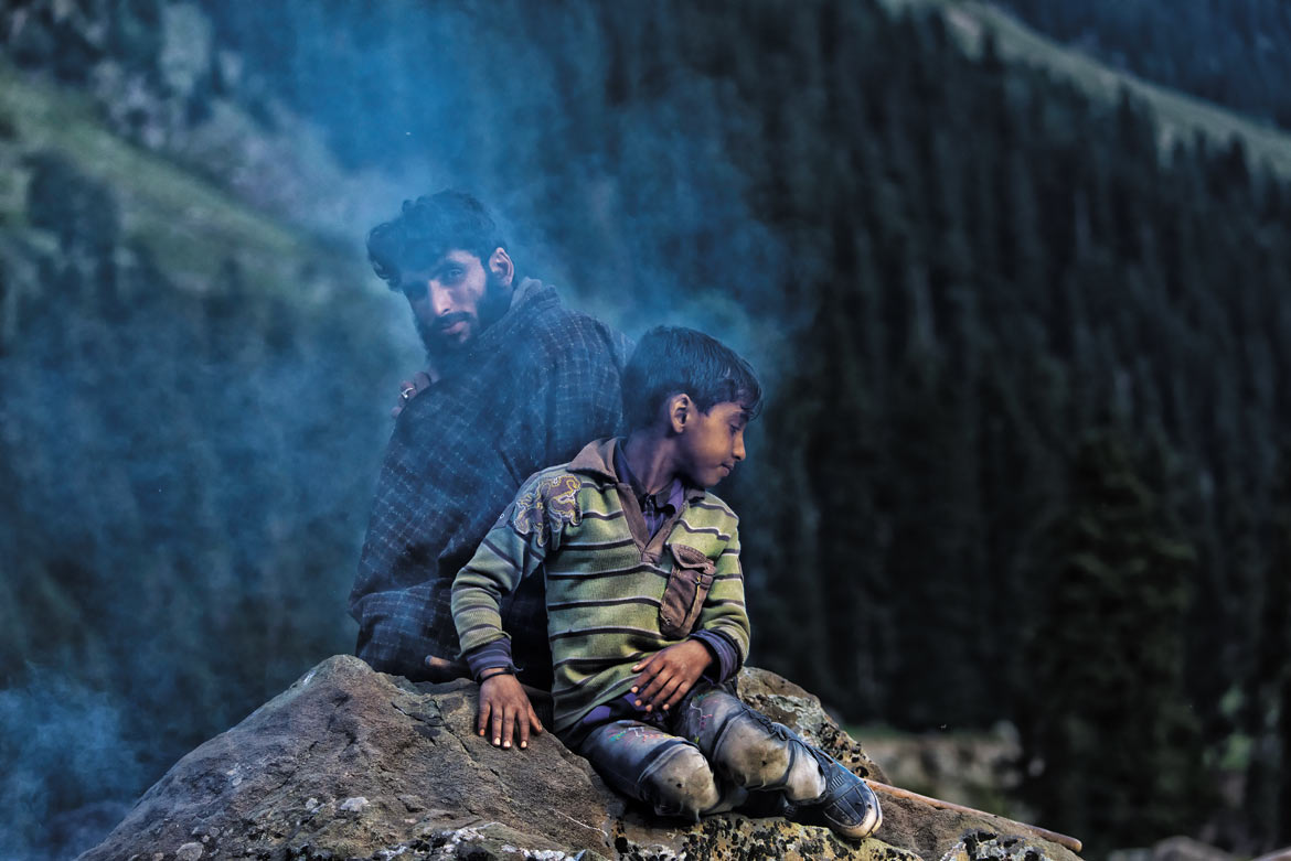 Mushtaq and Mateen, a father-and-son duo, warm themselves while waiting for dinner. The Bakarwals don't stock up on firewood as they never camp above the tree line