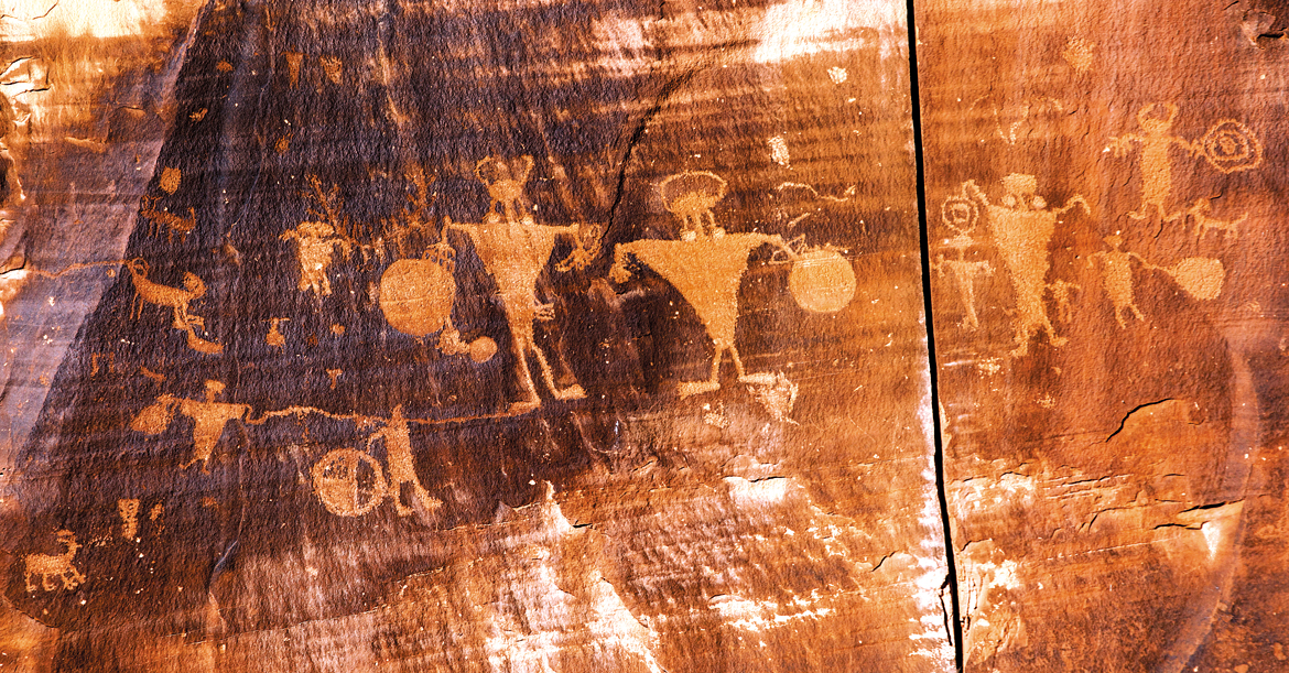 Petroglyphs of horned anthropomorphs holding shields, and abstract images form part of a 125-feet panel engraved on a sheer rockface, a short excursion from Moab in Utah