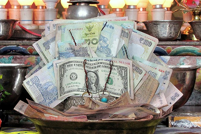 Reflecting tourist profile through currency, at Thiksey Monastery, near Leh town
