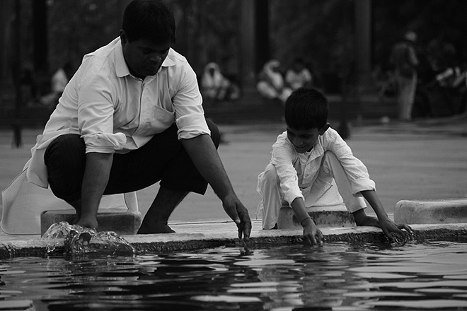 Discipline is a legacy. A father teaches his son how to wash his hands and feet properly before joining the namaz