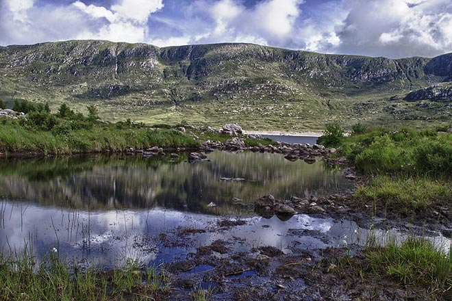 Meandering through the highlands, catch the blue sky and the mountains reflected in a lake