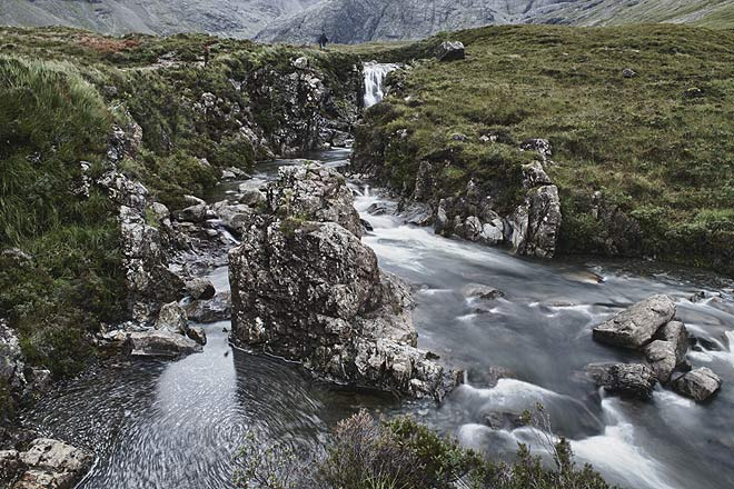 The flow of the water tumbling down the waterfall swirls around the massive rocks in the Fairy Pools, Isle of Skye
