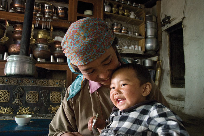 A mother with her son inside a traditional Ladakhi kitchen in Lamayuru
