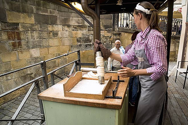 A young baker making trdlo in the Old Town area of Prague