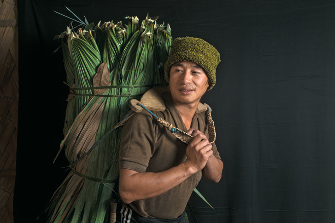 A Lisu man carrying leaves from the forest to help construct a neighbour's house in Nibudi