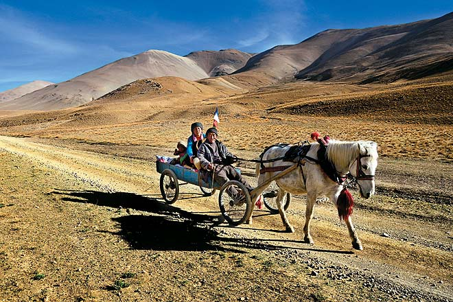 A farming family travels on a horse-drawn cart through the rugged mountain terrain of Central Tibet