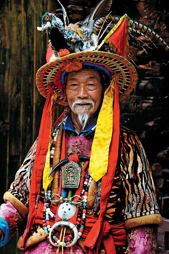 A Naxi tribal chief in Central Yunnan obligingly poses in ethnic regalia for this photograph