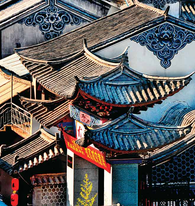 The ornate roofs of buildings glow in the afternoon sun in the ancient town of Dali in Yunnan