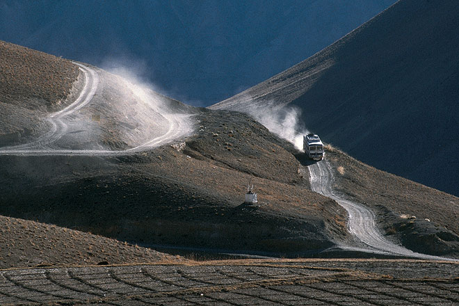 A bus passing through the bare terrain of Ladakh
