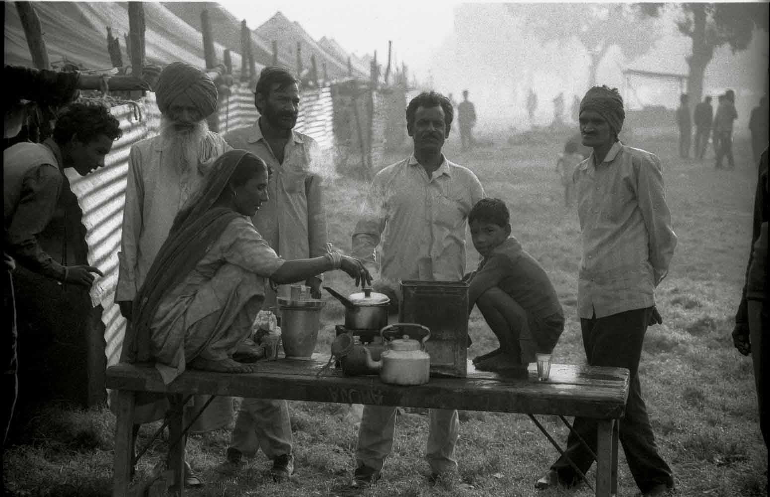 A woman makes chai for male workers before they set out for their morning shift at a tea factory