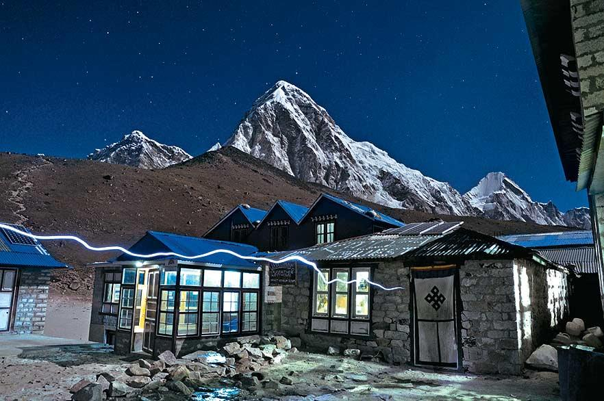 A trekker's headlamp leaves a white line in the moonlight while entering the lodge at Gorak Shep