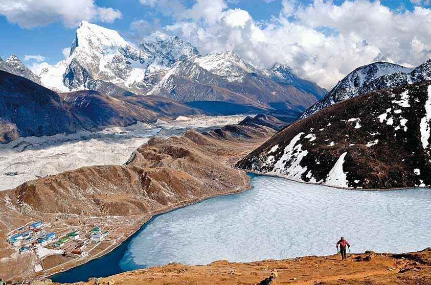 The lodges of Gokyo and the third lake is dwarfed by the huge bulk of Cholatse (6,440m) as a trekker makes her way up to Gokyo Ri