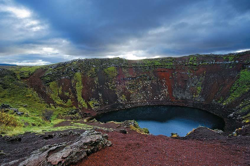 Kerid, a volcanic crater lake along the route to the popular 'Golden circle' is easily recognisable by its striking red volcanic rock and aquamarine water