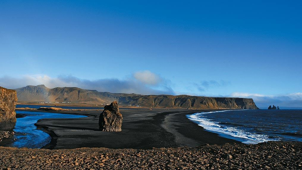 The promontory at Dyrholaey offers unhindered views over the black-sand beach Reynisfjara and the basalt projections of Reynisdrangur