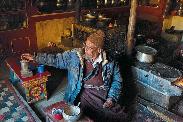 Tashi Stanba spins his prayer wheel at the Tanjuk homestay.