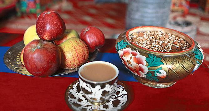 A repast of fresh apples from the orchard, yoors (a dried fruit and roasted grain mixture) served in a hand painted wooden zibor and butter tea.