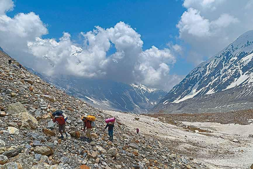 Porters make their way up the moraine on the lower Panpatia glacier. Progress is slow and painful on this stretch, with patches of snow offering some relief from the endless sea of loose rock and boulders.
