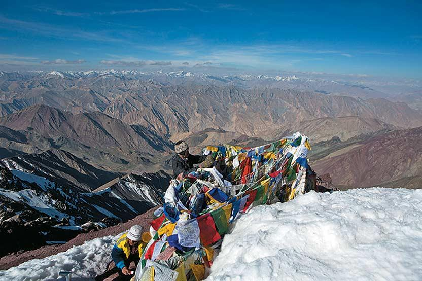 Expedition guides put up prayer flags on the summit of Stok Kangri