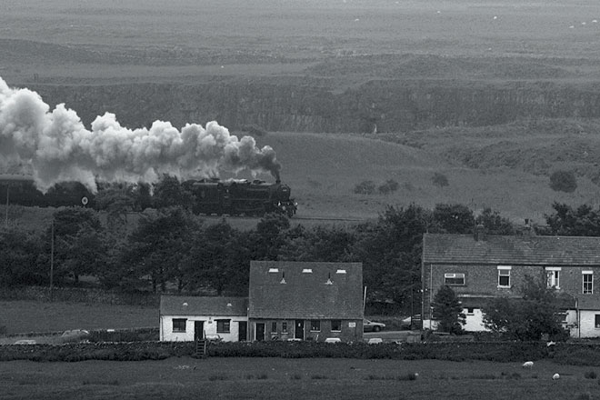 A steam train chugging through the countryside on its way to the Ribblehead viaduct