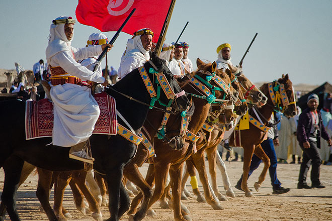 A Tunisian bedouin tribe in traditional attire hold aloft and occasionally shoot their ceremonial guns during the parade