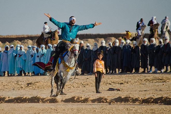 Blindfolded men show off by performing tricks on horseback