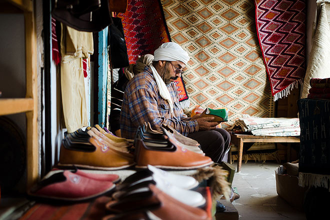 A man stitches traditional shoes in the main square