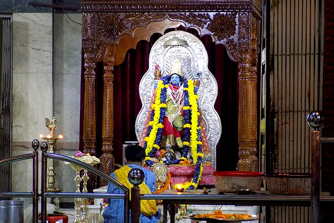 A pujari offers aarti to the idol of Goddess Kali