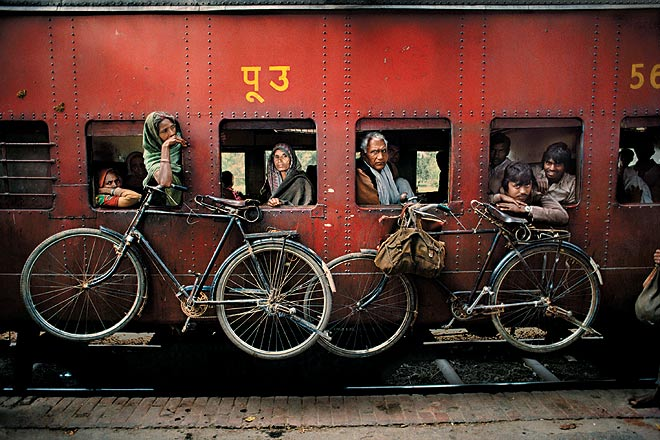 Bicycles hang on the side of a train. West Bengal, 1983