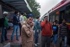 People wait for buses at a bus stand, in New Delhi.