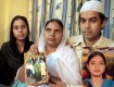 Shamima Kausar, mother of Ishrat Jahan (inset), holds a group photo of the family while standing with her daughter and son in Thane, Mumbai