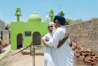 <b>Safe Custody</b> Joga Singh with a maulvi outside the mosque in Sarwarpur that his brother Sajjan helped reconstruct