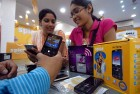 Customers check out phones at a Delhi store