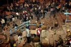 People look on as policemen and officials inspect the site of an explosion that rocked the holy town of Varanasi.