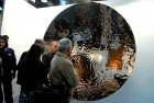Visitors capture their reflections on an Anish Kapoor work in stainless steel and resin