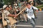 <b>Getting it</b> A news photographer tastes the police baton during the Anna Hazare stir