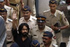 Policemen escort cartoonist Aseem Trivedi to a court in Mumbai.