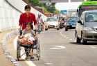 Disabled girl in a wheelchair crossing the road in New Delhi
