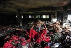 <b>Red rags</b> A worker walks amid burnt clothes at the factory in Dhaka where a fire killed eight on May 8