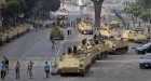 Egyptian army soldiers take positions on top and next to their armored vehicles while guarding an entrance to Tahrir square, in Cairo, Egypt