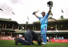 A fan prostrates before a wax effigy of his idol at the Sydney Cricket Ground