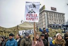 A woman holds a placard displaying a caricature of Russian President Vladimir Putin during a rally against Russia on Kiev's Independence square on March 2, 2014.