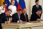 Mar 18, 2014: Russian President Vladimir Putin looks on as Crimean leaders, Speaker of Crimean legislature Vladimir Konstantinov, second left, Crimean Premier Sergei Aksyonov, left, and Sevastopol mayor Alexei Chalyi, right, sign a treaty for Crimea to join Russia in the Kremlin in Moscow.